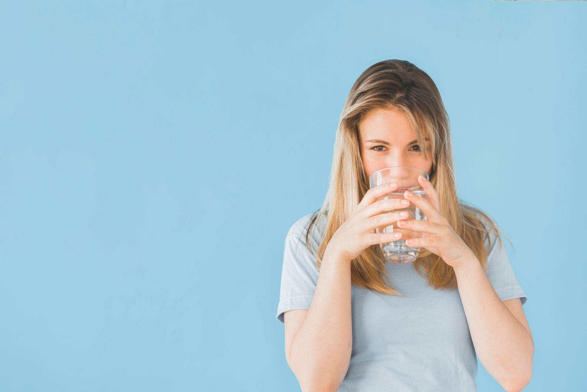 Mulher feliz bebendo água. (Reprodução/Freepik)