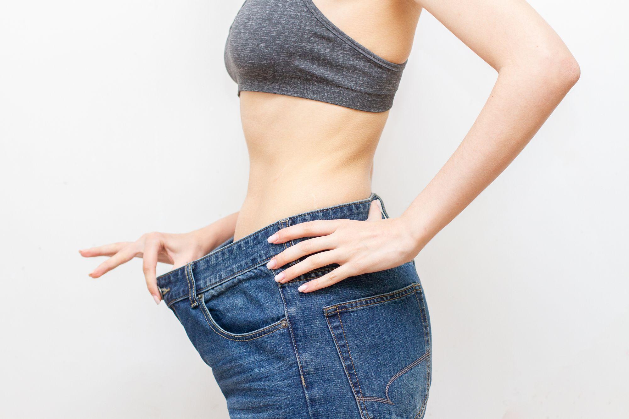 Mulher com calça grande após perder peso. (Reprodução/Freepik)